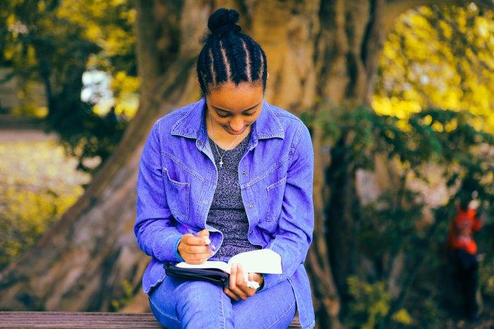 girl-writing-at-park