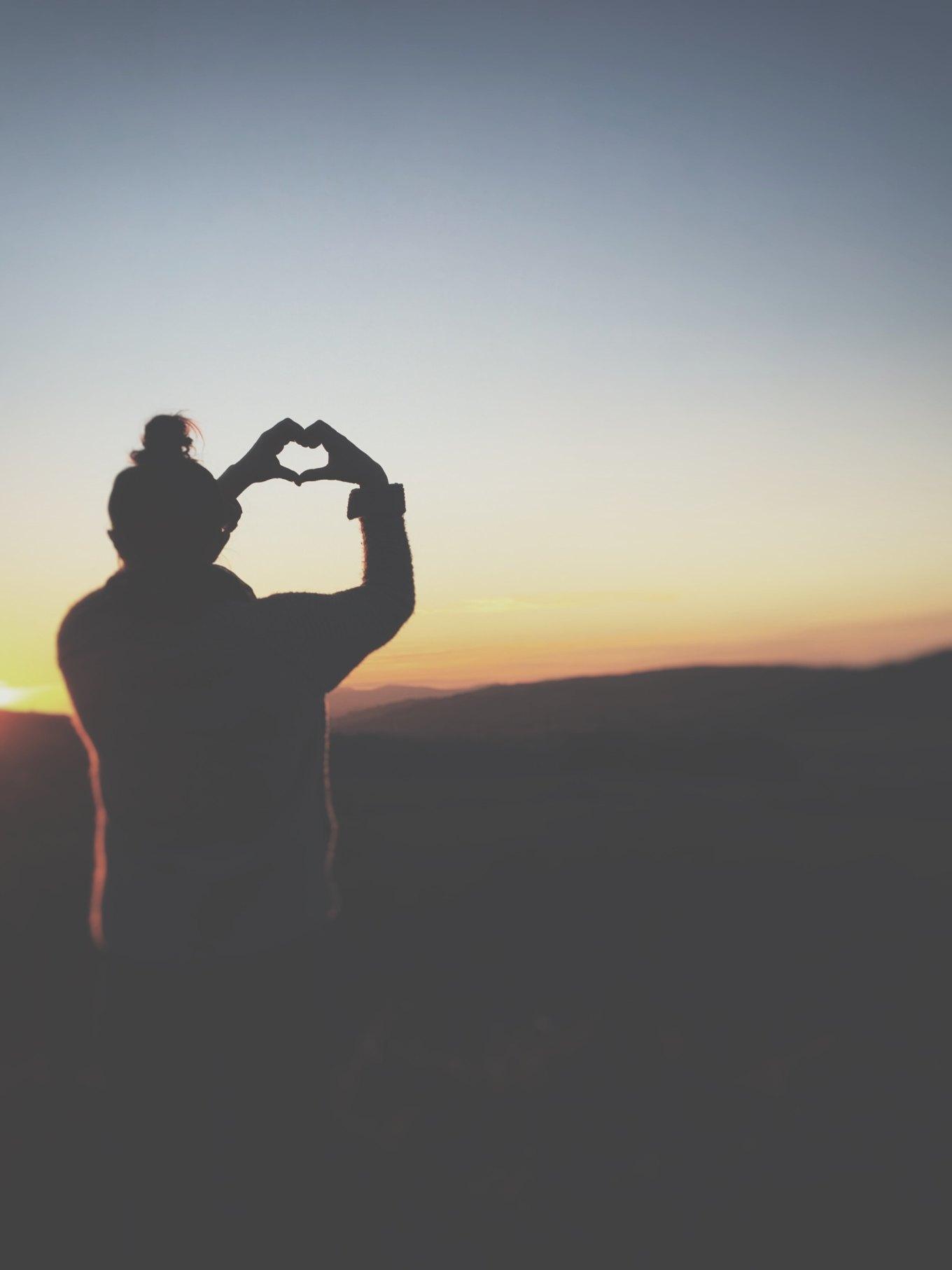 woman-heart-hands-sunrise
